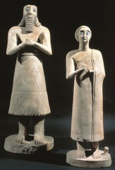 Title/ Designation: Statues of votive figures, from Square Temple at Eshnunna (Modern Tell Asmar, Iraq) Artist/Culture: Sumerian Date of Creation: c. 2,700 BCE Materials: Gypsum inlaid with shell and black limestone